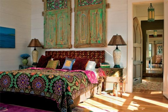 The master bedroom features Balinese windows and rich fabrics. Midway down the hall, a salvaged Gothic door opens to the powder room.