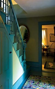 Simply painting the trim a period color turns this quiet back stair into an architectural statement. A mirror provides extra light.