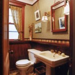 This Chicago bathroom has a historical feel, done up in a dark wood wainscot and checkerboard floor. Art and mirror hang from a picture molding, a nice detail.