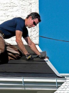 After laying 30# tar paper over the front drip-edge, Mark traps the gable end with another drip-edge, fastening it with staples.