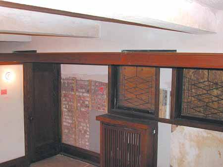 In the playroom of Frank Lloyd Wright's Robie House, newly installed air-supply diffusers just below the ceiling hide behind original wood trim that was cut back at 45 degrees, sealed, and reinstalled. Plywood protects the windows during exterior restoration.