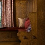 An oak banquette is built into the wainscot in an Arts & Crafts Tudor house.