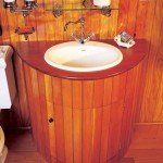 In an attic bathroom in a shingled seaside house, varnished mahogany tops a nautical cabinet made of fir beaded board.