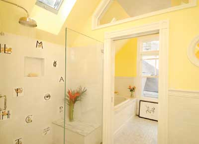 When carving out a bathroom in the attic of an 1890s Shingle Style house, contractor Charlie Allen worked with the room's geometry to help bring natural light into the space, adding a skylight above the shower stall and a trapezoidal transom above the doorway between the two rooms.