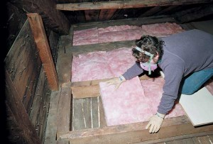 Placing fiberglass batts between existing attic timber joists reduces heat loss; be sure to wear proper skin protection when handling insulation.