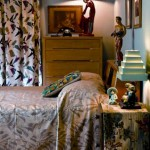 In the bedroom, walls were painted a restful blue (a custom mix). The blond Heywood–Wakefield bedroom set, which had belonged to Karen's parents, has an appreciative new home. Bark-cloth curtains are printed with boomerangs.