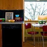 Period color marks the kitchen, especially the cherry-red vinyl of the chrome dinette set; vintage bowls in turquoise, celery green, and sunshine yellow are a foil for the gray and black countertop area.