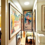 An upstairs view down to the breakfast nook is a riot of poster art; several of the large pieces were framed specifically for this stair hall.