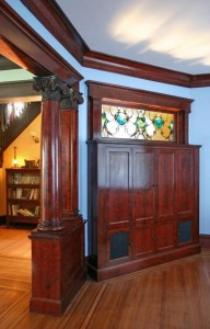 A custom, built-in TV cabinet was created to reclaim a space where a wall was long-ago removed. To channel the feel of the dining room's buffet, it's topped by a stained glass window featuring an abstract pattern of cats and dogs. The result complements the room's grand original Composite Order columns.