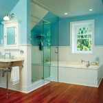 The glass shower stall and whirlpool tub in this Colonial Revival bath are modern amenities, but the warm wood floor, white beadboard, and marble-topped washstand keep the room in line with the age of the house.