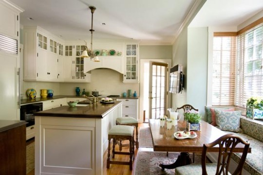 Custom-built white cabinets are complemented by a soft green wall and an upholstered window seat in the kitchen of a 1915 Colonial Revival.