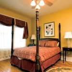 Sunny yellow walls complement period furnishings in a bedroom.
