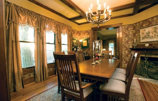 The restored dining room includes homemade draperies, refinished woodwork, and the excavated fireplace.