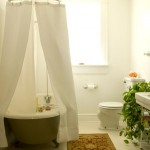 White, bright, and intentionally simple, the focal point of the main-level bathroom is undoubtedly the claw-foot tub. The couple plans to restore the dropped ceiling to its original height.