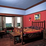 "The picture rail and sconces in the bedroom are originals; updated paint colors help the woodwork stand out, and form a nice backdrop for a collection of ""Grueby green"" pots."