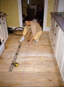 Popping a carpenter's chalk line (above) helps to center the pattern across the floor and keep tiles in alignment.