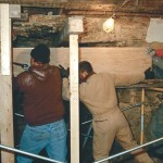 Inside the basement, the crew slides the new lintel in place over the hearth using levers and muscle.
