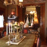 The dining room (in the foreground, with the music room beyond) does not have electric fixtures. The wallpaper is from Thibaut's Historic Home Collection. Note the double portiere; a beaded valance faces the dining room.
