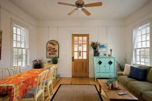 The interiors are kept casual with a mix of vintage furnishings and artwork. Wood floors are covered in beach grass rugs for a seaside atmosphere.