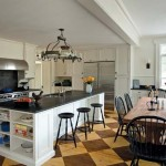 The eat-in kitchen offers unadorned cabinetry, painted floors, and a farmhouse table to create a country atmosphere.