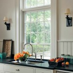 So that the correct window proportions are not interrupted on exterior of the house, the windows extend below the kitchen cabinetry.