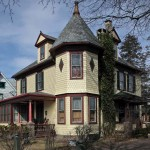 A slate roof, clapboards, and fancy-cut shingles mingle on the Queen Anne tower house.