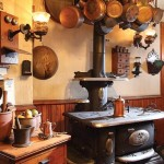 Copper pans and antique light brackets surround the working stove that came from the guest house next door.