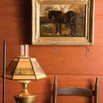 A Victorian-era painting by William Preston Phelps of a handsome black horse hangs over a slat-back chair in the keeping room.