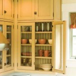 Glass-fronted cabinets that reach to the ceiling molding recall 19th-century farmhouse kitchens and butler's pantries.