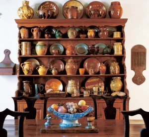 Redware fills a dresser at Cogswell's Grant, an 18th-century farmhouse with a large folk-art collection.