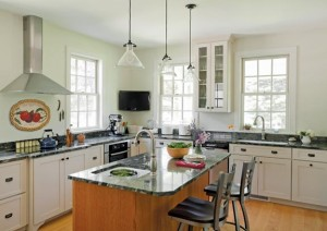The kitchen is outfitted with simple cabinetry; a center island and flat-screen TV reveal the space's contemporary side.