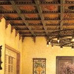Decorated beams crown a southwestern Mission Revival dining room.