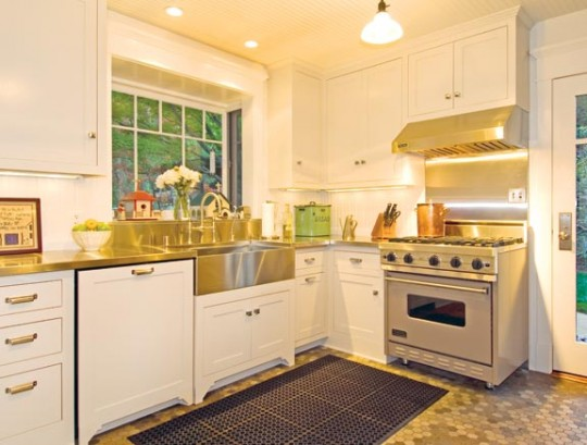 """The kitchen, in white and stainless steel, captures the look and spirit of """"sanitary"""" kitchens of the early 20th century."""