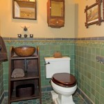 Deep greens and browns soften the downstairs powder room; vintage tramp-art accessories and pine-cone and bear relief tiles add texture.