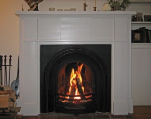 The restored fireplace,  with a new insert and two cast-in-place flue liners in  the chimney, now safely vents two appliances—hot water heater and boiler—in addition to holding a crackling fire.