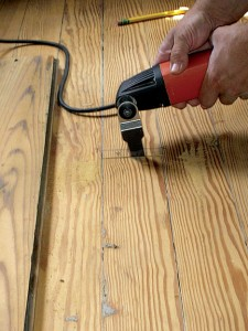 To replace a damaged floorboard, start by marking off the damaged material, then cutting it directly over the floor joist using an oscillating saw. You can then remove the damaged board.