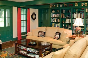 With green walls, cream-colored furniture, and red accents, the family room is a cozy hideaway where the couple spends the majority of their time.