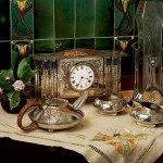 An enameled clock by George Walton; vases from German silverplate manufacturer WMF; stylized Celtic-design tea service by Archibald Knox.