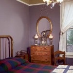 Strong period colors of royal purple and mossy green enliven the small guest bedroom.