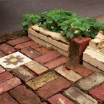 Recycled brick and architectural fragments embellish the parking strip.