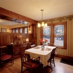 The formal dining room was separated from the adjacent family space with a paneled, three-quarter-height wall. It serves both as a space-dividing element and as built-in furniture.
