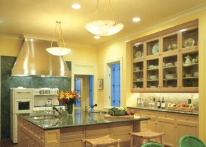 In this kitchen, semi-indirect bowls provide ambient light over the island, aided by a discreet pair of recessed can lights in the ceiling. Counter task light, however, comes from under-cabinet fixtures. Note the glazed upper cabinets—a good place for accent lights. (Courtesy: MIchael Bruk)