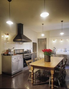 In a large kitchen devoid of cabinets and the opportunities they offer to hide light sources in soffits, multiple pendants hanging to the 7' level contribute ambient light and ambiance, while period sconces direct task light to work areas over counters, stove, and sink. (Courtesy: Dub Rogers)