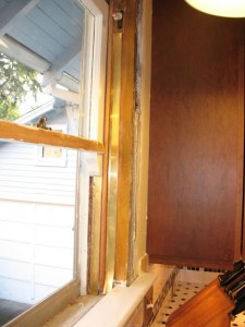 The brass flange installed here is one of many ways to tighten up drafty areas around windows.