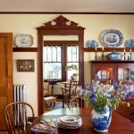 A collection of antique transferware is comfortably displayed in the dining room sideboard and on the plate rail.