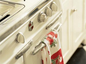 Cherry and apple reds on a vintage kitchen towel add a pop of color to a creamy white 1950s-era range.
