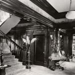 In the archival photo, carpeting covers the entry hall floor.