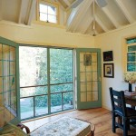 The studio's high ceiling creates spaciousness. Screen doors open to the meadow.