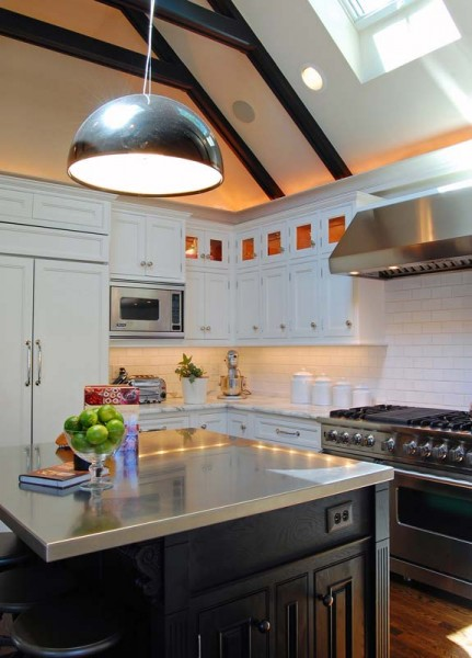 A subway-tile backsplash, marble countertops, and illuminated display cabinets help to ground this modern Foursquare kitchen in tradition.