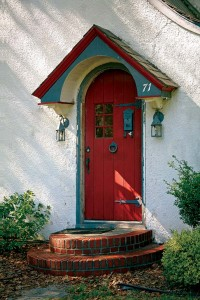 The arched board door sheltered by a small gabled hood is part of the English-cottage image of the Village.